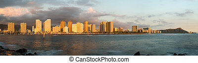 Panorama of the skyline of Honolulu and Waikiki from Ala Moana park as the sun sets and illuminates the facades of the hotels and apartments