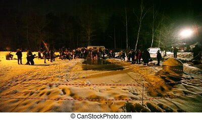 panorama of winter ice-hole in night from people around