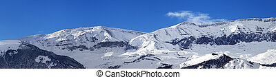 Panorama of winter snowy mountains at sunny day