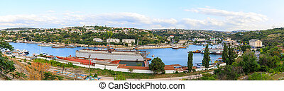 Panorama of Yuzhnaya bay in Sevastopol, Ships of the Black Sea Fleet of Russia and view to the factory and the city