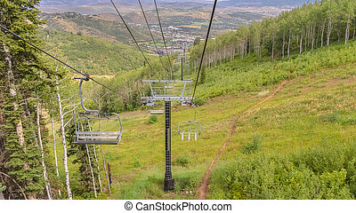Panorama Off season in Park City with hiking trail amid grasses and chairlifts overhead