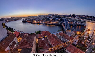 Panorama old city Porto at river Duoro, with Port transporting boats after sunset day to night timelapse, Oporto, Portugal