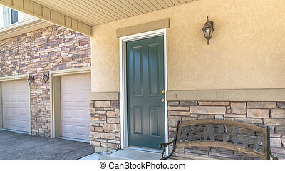 Panorama Old porch bench against stone brick wall of home with green wood front door