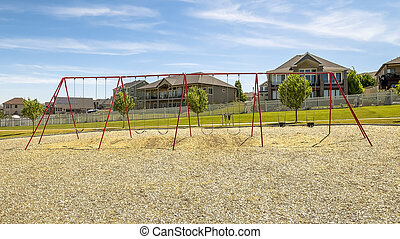 Playground with swings and picnic pavilion under blue sky on a sunny day