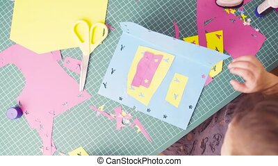 Hands of little girl gluing colored paper - Panorama. Top...