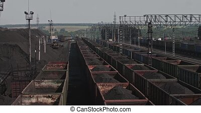 Panorama trains loaded with coal. Railway cars at the station with ore. Carriages on loading of minerals. Loaded wagons on railway. Empty railroads cars on industrial railway terminal