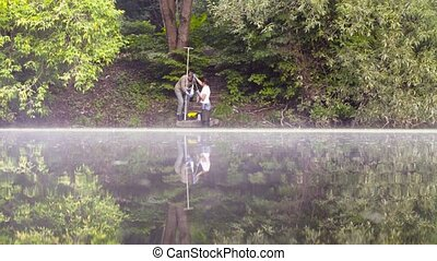 Two ecologist getting samples of water in city park -...