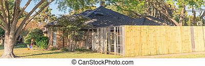 Panorama view front yard of corner house with wooden fence replacement in progress suburbs Dallas, Texas, USA