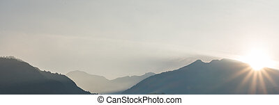 panorama view of a mountain landscape in silhouette with the sun setting