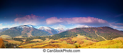 Panorama view of snow capped mountain peaks in spring