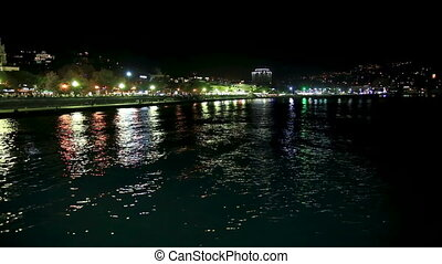 Panorama view of Yalta town from the Black sea. Night life on embankment. Crimea