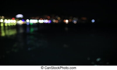 Panorama view of Yalta town from the Black sea. Night life on embankment. Defocused lights. Crimea, Russia.