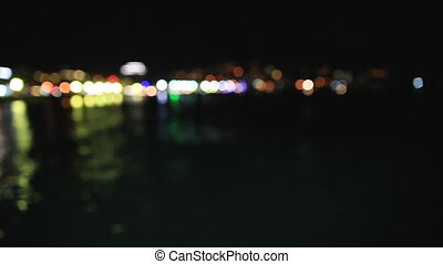 Panorama view of Yalta town from the Black sea. Night life on embankment. Defocused lights. Crimea