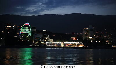 Panorama view of Yalta town from the Black sea. Night life on embankment. View from moving boat.Crimea