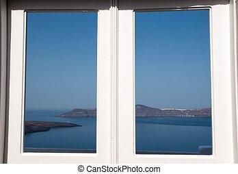 Panorama view to the caldera of Santorini through the white window