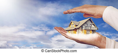 Panorama with a house on hands - House on hands in front of...