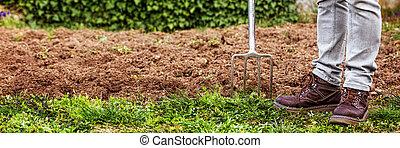 man holding a gardening fork, sticking in the ground