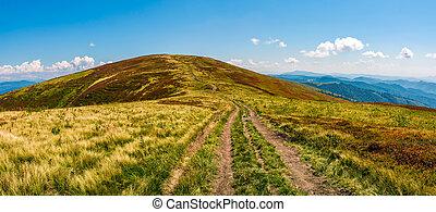panorama with dirt road through mountain ridge - panorama...