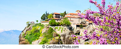 Panorama with unfocused Great Meteoro Monastery in Meteora and Branch of pink blossom