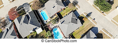 Panoramic aerial view a rich subdivision neighborhood with swimming pool and bright autumn leaves