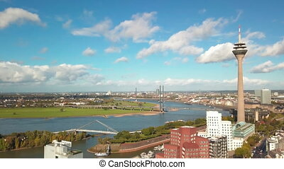 Panoramic aerial view of a waterfront of the Rhine river in Dusseldorf with famous TV tower Rheinturm on the river bank 4K