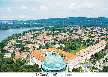 Panoramic aerial view over the roofs of Esztergom town near Budapest, Danube river and a tower of Esztergom Cathedral at the foreground.