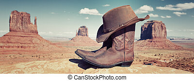 boots and hat in front of Monument Valley, USA, panoramic view