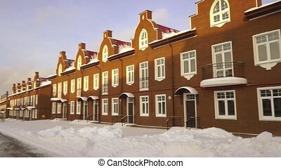 Panoramic establishing shot of red brick townhouses at sunny snowy day