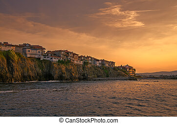 evening view of a small town on rock cliff at sunset -...
