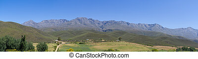 Panoramic farm landscape with high mountains and fields