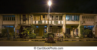 Panoramic image of heritage houses and trishaw under...