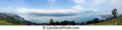 Broad panoramic landscape of the Otago Peninsula and Bay with the city of Dunedin in the distance and clouds hanging over the mountains