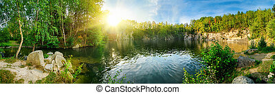Panoramic landscape shot of idyllic lake surrounded by trees and cliffs, with the sun glowing on the horizon