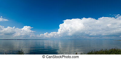 panoramic landscape with calm sea and impressive clouds reflecting in the water
