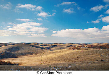 Panoramic landscape with hills and blue sky.