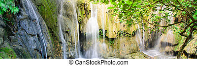 Panorama view jungle waterfall cascade Thac Voi at tropical rainforest in Thanh Hoa province, Vietnam. Current stream gushing through cascade tiers into emerald pond with by mature trees