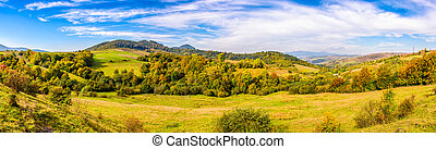 panoramic meadow on hillside of mountain range - early...