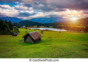 Panoramic morning scene of Wagenbruchsee (Geroldsee) lake with Zugspitze mountain range on background. Amazing autumn view of Bavarian Alps, Germany, Europe. Wooden hut on meadow by Geroldsee lake.