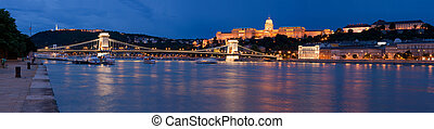 Panoramic night cityscape on landmark Gellert and castle hill Buda, baroque royal palace, Szechenyi chain bridge over Danube river in twilight Budapest Hungary