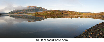 Panoramic of hills reflected in surface of lake foggy morning