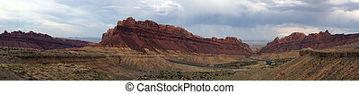 Panoramic of Road winds through Spotted Wolf Canyon with dramatic clouds in sky