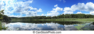Panoramic pond view in summer, clouds reflected in still ...
