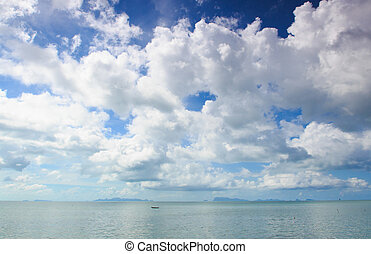 Panoramic seascape with puffy white clouds, blue sky and ...