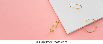 Panoramic shot of three modern golden bracelets on white and pink background with copy space
