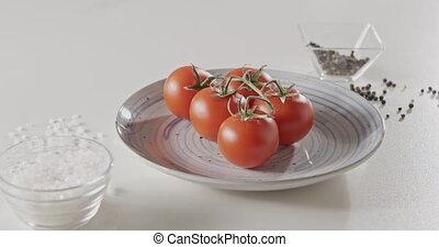 Panoramic slow motion video in 4K, close-up of cherry tomatoes on a blue ceramic plate on a white kitchen table, pepper and salt in a glass jar.