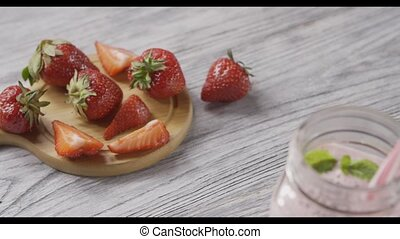 Panoramic slow motion video of jar with strawberry milk...