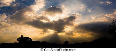 Panoramic sunset with clouds in the twilight sky with mountain silhouette