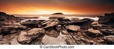 Surf rolling in over rocks