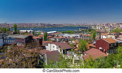Panoramic top view with red roofs of houses and mosques behind Golden Horn timelapse in Istanbul, Turkey. Ferry ships sail up and down the Golden Horn.