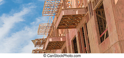 Panoramic upward view of multistory apartment building with patio under construction near Dallas